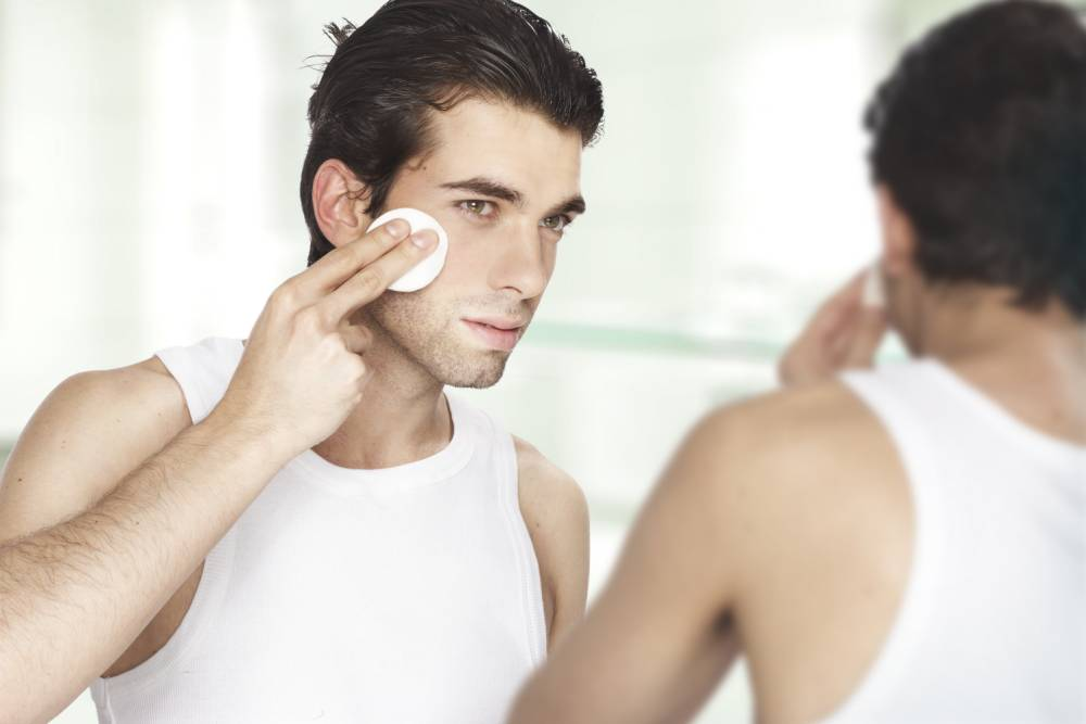Man looking at his reflection; using facial toner
